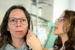 Quadro cabendo dos vidros do olho do paciente bonito novo da mulher com o ?tico do optometrista do oftalmologista foto de stock