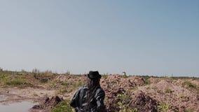 Quadro cinemático no mo lento Um assassino cloaked está perseguindo alguém através do deserto video estoque