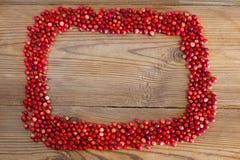 Quadro com as airelas vermelhas das bagas em um de madeira Imagens de Stock Royalty Free
