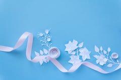 Quadro com as flores do Livro Branco e fita cor-de-rosa no fundo azul Corte do papel Fotografia de Stock Royalty Free