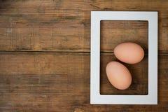 Quadro com dois ovos para dentro na textura de madeira marrom do fundo foto de stock