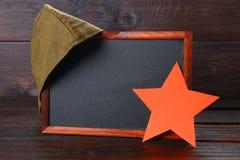 Quadro com espaço vazio, o tampão militar e a estrela vermelha em uma madeira Foto de Stock