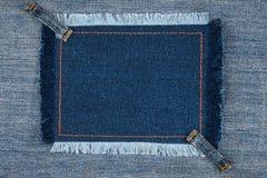 Quadro com franja e com as duas calças de brim das correias, mentiras na sarja de Nimes azul, com espaço para seu texto Fotografia de Stock Royalty Free