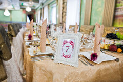 Quadro com número sete na tabela do convidado no restaurante do casamento Fotografia de Stock
