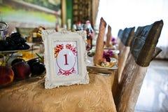 Quadro com número um na tabela do convidado no restaurante do casamento Imagem de Stock