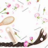 Quadro com o pente para a denominação do cabelo, o prendedor de cabelo e flores cor-de-rosa no fundo branco Composição do blogue  Foto de Stock