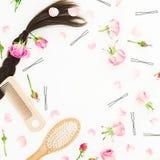 Quadro com os pentes para a denominação do cabelo, o prendedor de cabelo e flores cor-de-rosa no fundo branco Composição do blogu Fotos de Stock