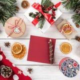 Quadro criativo feito de ramos de árvore do Natal, nota da disposição do cartão de papel, cones do pinho, presentes, camiseta do  fotos de stock