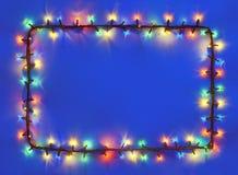 Quadro das luzes de Natal na obscuridade - fundo azul fotografia de stock royalty free