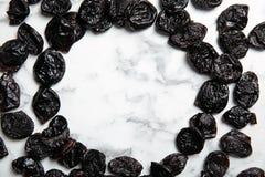 Quadro de ameixas secadas doces no fundo de mármore imagem de stock royalty free