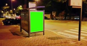 Quadro de avisos com uma tela do verde da chave do croma em uma rua da noite da cidade dos carros do tráfego, noite clara, propag