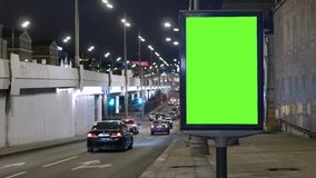 Quadro de avisos com uma tela verde, situada em uma rua movimentada Os carros movem-se na noite video estoque