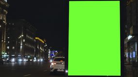 Quadro de avisos com uma tela verde, situada em uma rua movimentada Os carros movem-se na noite vídeos de arquivo