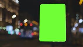 Quadro de avisos com uma tela verde, situada em uma rua movimentada Os carros movem-se na noite O fundo é fora de foco filme
