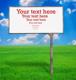 Quadro de avisos em branco em um fundo da grama e do céu Foto de Stock
