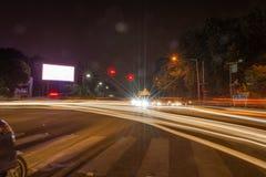 Quadro de avisos vazio na estrada durante a noite com fundo da cidade com o trajeto de grampeamento na tela - pode ser usado para imagens de stock
