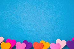Quadro de corações de madeira coloridos na parte inferior em um backgroun azul Fotografia de Stock Royalty Free