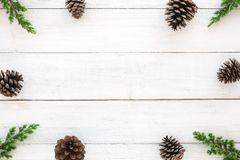 Quadro de Hristmas feito das folhas do abeto e de elementos rústicos da decoração dos cones do pinho em de madeira branco Fotografia de Stock