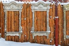 Quadro de janela de madeira antigo no estilo do russo como o elemento decorativo em uma cerca vermelha feita das placas cobertas  Fotografia de Stock