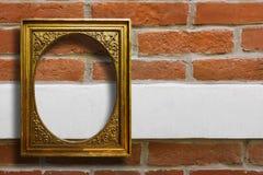 Quadro de madeira dourado para imagens na parede de tijolo velha Imagens de Stock Royalty Free