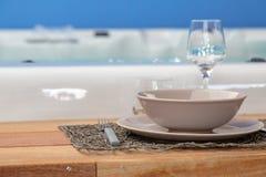 quadro de madeira em torno de um Jacuzzi com faqueiro para jantares luxuosos imagem de stock