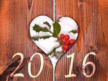 2016, quadro de madeira na forma de um coração e ramo do azevinho sob a neve Foto de Stock Royalty Free