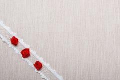 Quadro de rosas de seda vermelhas no pano Imagem de Stock Royalty Free