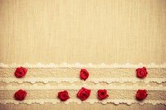 Quadro de rosas de seda vermelhas no pano Imagens de Stock