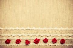 Quadro de rosas de seda vermelhas no pano Fotografia de Stock Royalty Free