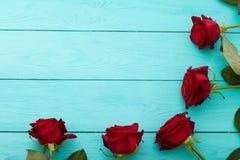 Quadro de rosas vermelhas no fundo de madeira azul Imagem de Stock Royalty Free
