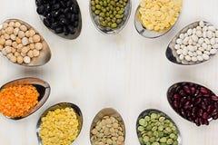 Quadro decorativo de feijões diferentes da variedade nas colheres com espaço da cópia no fundo de madeira branco Fotografia de Stock Royalty Free