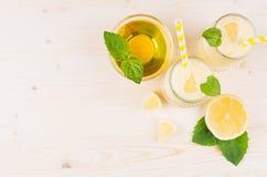Quadro decorativo do batido amarelo do limão nos frascos de vidro com palha, folha da hortelã, limão cortado, mel, vista superior Fotografia de Stock Royalty Free