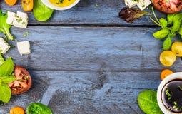 Quadro do alimento com ingredientes da salada: óleo, vinagre, tomates, manjericão e queijo no fundo de madeira rústico azul Foto de Stock
