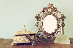 Quadro do estilo do victorian, garrafa de perfume e neckless vazios antigos na tabela de madeira imagem filtrada retro Fotos de Stock