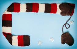 Quadro do inverno com mitenes, lenço e os flocos de neve pequenos Imagem de Stock