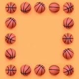 Quadro do muitas bolas alaranjadas pequenas para o jogo do esporte do basquetebol encontra-se no fundo da textura do papel alaran imagem de stock