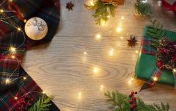 Quadro do Natal, do ano novo com teste padrão escocês da tartã e luzes festivas no fundo de madeira fotos de stock royalty free