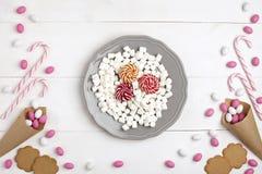 Quadro doces, cookies, marshmallows e pirulitos no fundo de madeira branco da opinião superior da placa Fotografia de Stock