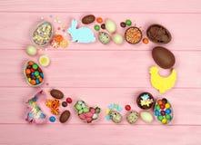 Quadro dos ovos da páscoa e dos doces do chocolate em um fundo cor-de-rosa foto de stock royalty free