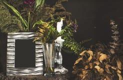 Quadro e flores da foto do vintage na tabela de madeira sobre do grunge do fundo o estilo de vida ainda Fotografia de Stock Royalty Free
