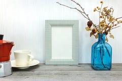 Quadro e vaso vazios da foto com as flores pressionadas em b de madeira cinzento Fotos de Stock Royalty Free