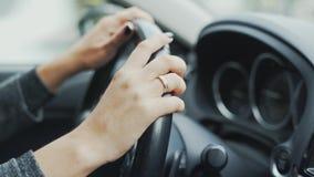 Quadro envolvido close-up As mãos de uma menina casada no volante do carro Conceito da condução, carro, mulher filme