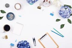Quadro feminino do espaço de trabalho da mesa com arranjo da beleza de hortênsias do ramalhete, de prancheta, de copo de café, de imagens de stock