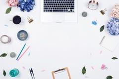 Quadro feminino do espaço de trabalho da mesa com arranjo de hortênsias do ramalhete, portátil da beleza, prancheta, caderno, gra imagens de stock