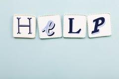 Quadro indicador da ajuda Palavra escrita à mão das letras das cores Luz - backgroun azul imagem de stock royalty free