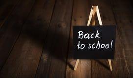 Quadro-negro com de volta a texto de escola, fundo de madeira escuro, espaço da cópia fotos de stock