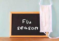 Quadro-negro com a estação de gripe da frase escrita nele e na máscara protetora Imagens de Stock Royalty Free