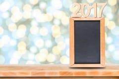 Quadro-negro com na tabela de madeira com fundo borrado do bokeh Imagem de Stock