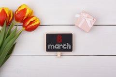 Quadro-negro com o 8 de março na tabela, ramalhete das tulipas Fotos de Stock Royalty Free
