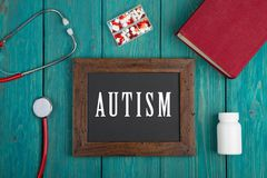 Quadro-negro com texto & x22; Autism& x22; , livro, comprimidos e estetoscópio no fundo de madeira azul fotos de stock royalty free